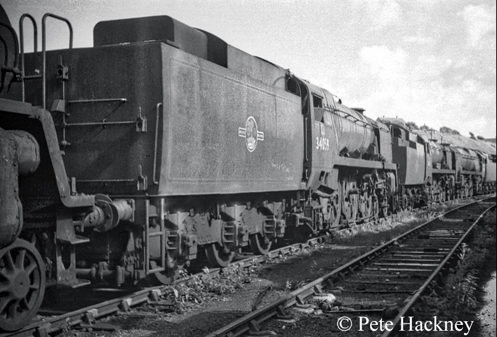 34059 Sir Archidald Sinclair in front of 34101 Hartland and 35022 Holland America Line in Woodham's scrapyard at Barry - July 1968.jpg