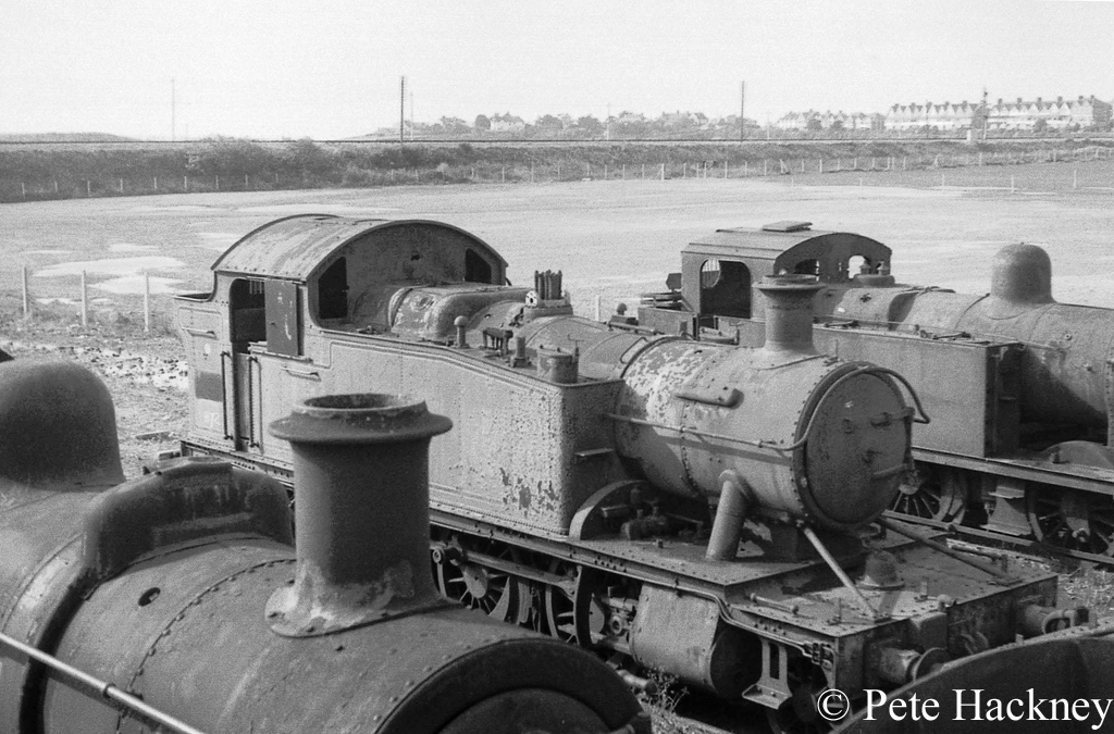 5572 in Woodham's scrapyard at Barry. The chimney in the foreground belongs to 46428 and the Jinty in the background is 47406 - October 1968.jpg